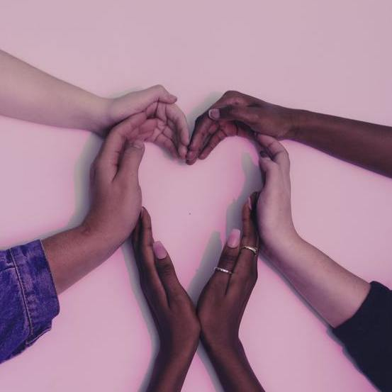 Six hands of people of various races, shaped together forming a heart on white background; purplish light over whole image