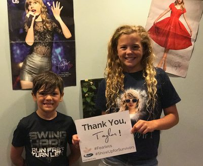 Two kids stand in front of Taylor Swift posts holding sign that says Thank You, Taylor!