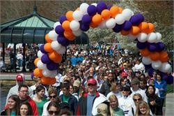 Large stream of participants at a previous Walk for Change with purple, orange, and white balloons
